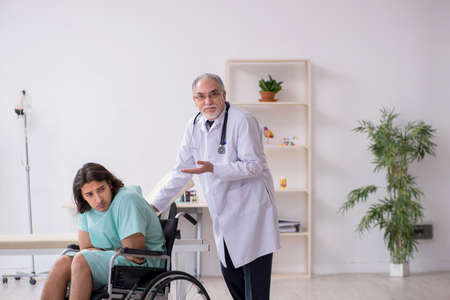 Young male patient in wheel-chair and experienced doctor traumatologist