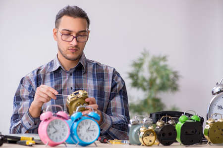 Young male watchmaker working in the workshop