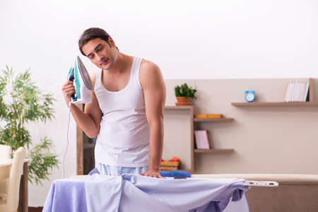 Young male employee ironing in the morning Reklamní fotografie