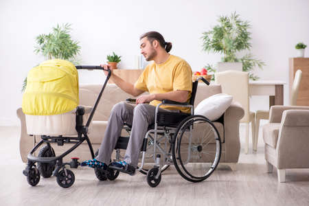Young man contractor in wheel-chair looking after newborn Zdjęcie Seryjne