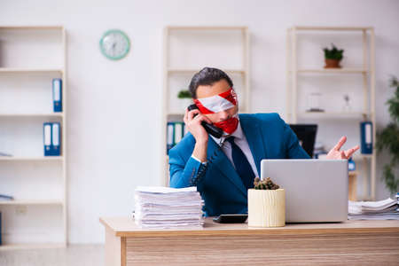 Mouth and eyes closed male employee working in the office