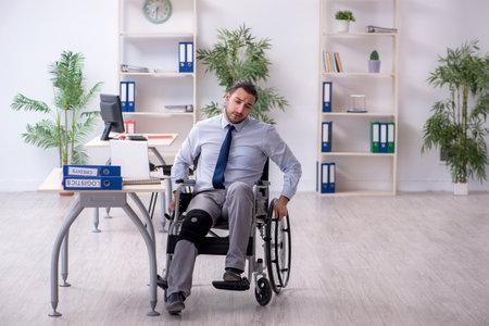 Young leg injured employee working in the office Zdjęcie Seryjne
