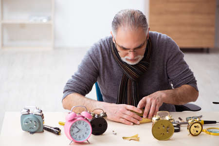 Old male watchmaker working in the workshop