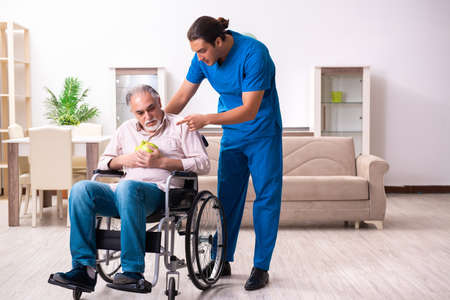 Old man in wheel-chair and young bad caregiver indoors Zdjęcie Seryjne