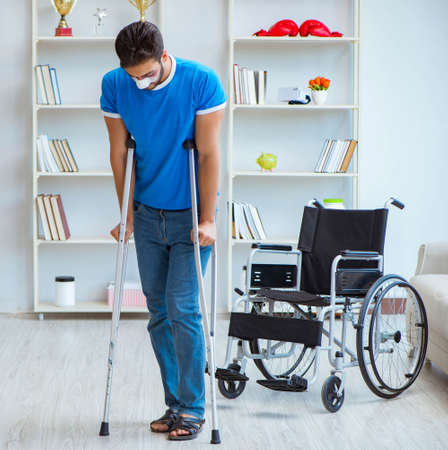 Young man recovering after surgery at home with crutches and a wheelchair