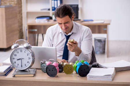 Young male employee afraid of missing deadline at workplace