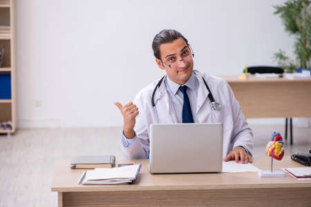 Young male doctor lecturer cardiologist working in the clinic 免版税图像