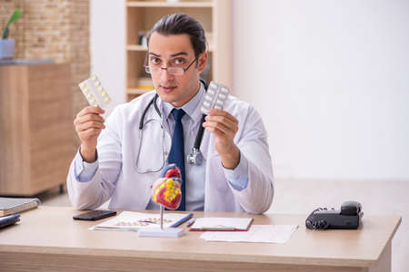 Young male doctor cardiologist suggesting pills 免版税图像