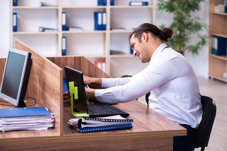 Young male employee unhappy with excessive work in the office 免版税图像