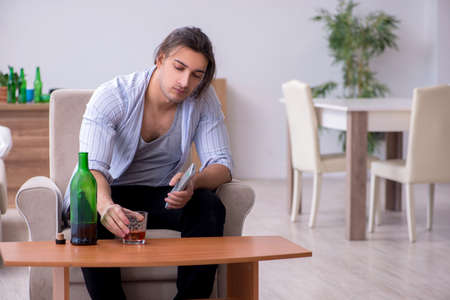 Young male alcoholic watching tv after party