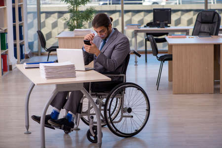 Young male employee in wheel-chair working in the office