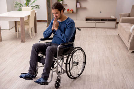 Young man in wheel-chair suffering at home Фото со стока