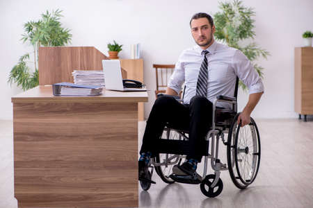 Young disabled employee suffering at workplace Фото со стока