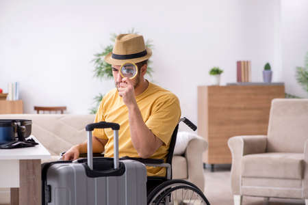 Young man in wheel-chair preparing for departure at home