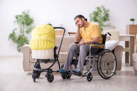 Young man contractor in wheel-chair looking after newborn Фото со стока
