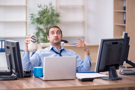 Young male employee holding moneybag in the office