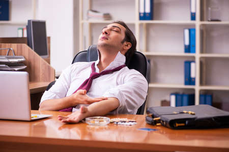 Young drug addicted male employee working in the office