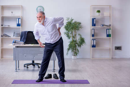 Aged male employee doing physical exercises during break 免版税图像