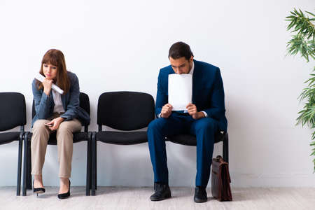 Young businessman and businesswoman waiting for an interview at