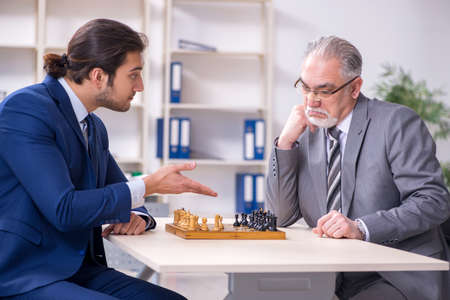 Two businessmen playing chess in the office 免版税图像