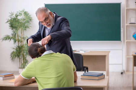 Aged teacher and male lazy student in the classroom 免版税图像