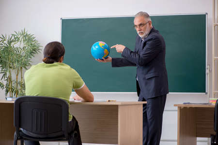 Aged geography teacher and male student in the classroom