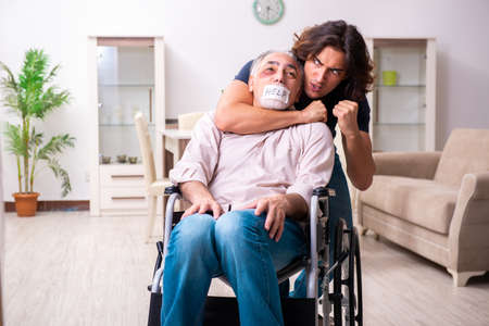 Old man in wheel-chair and young bad caregiver indoors 免版税图像