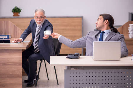 Old boss and young male assistant in the office