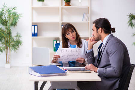 Young female doctor and sick businessman in the office