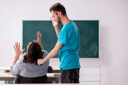 Two male pupils in bullying concept in the classroom
