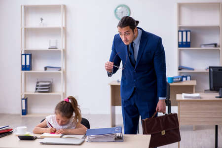 Young male employee and his little girl in the office