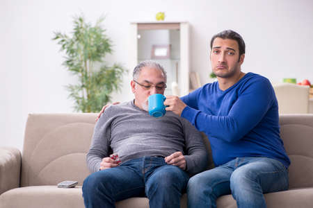 Young man looking after his sick father 免版税图像