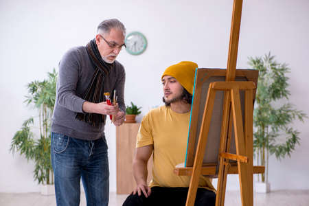 Young man taking lesson from old painter 免版税图像