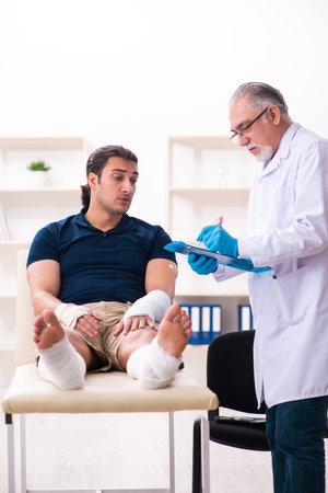 Young injured man visiting old doctor traumatologist 免版税图像