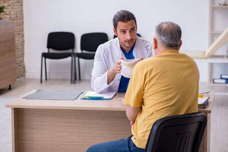 Old neck injured man visiting young male doctor