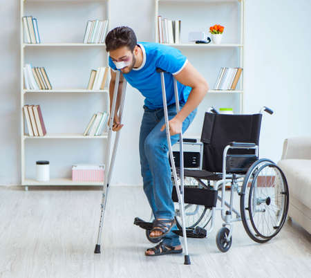 Young man recovering after surgery at home with crutches and a w Фото со стока