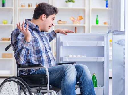 Young disabled injured man opening the fridge door Фото со стока