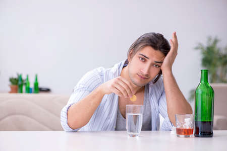 Young male alcoholic drinking whiskey at home Stockfoto