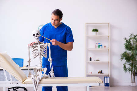 Young male doctor lecturer demonstrating skeleton Standard-Bild