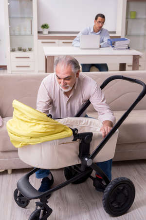 Retired grandfather looking after newborn at home