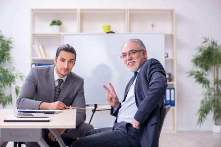 Old and young businessmen in business meeting concept