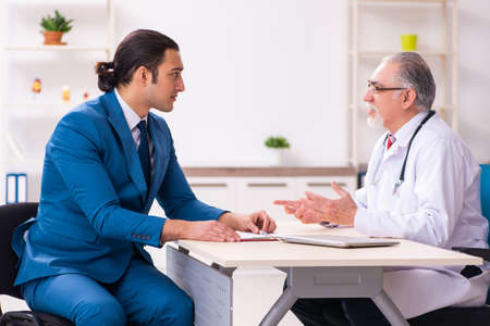 Young businessman meeting with old doctor