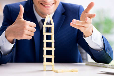 Young businessman building domino tower in office