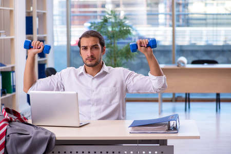 Young male employee doing sport exercises in the office