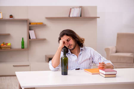 Young male student drinking alcohol at home