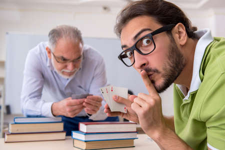 Old male teacher and young male student playing card in the clas