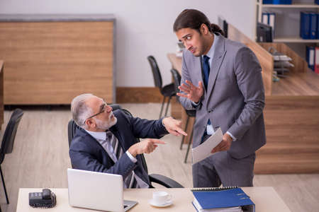 Old boss and young male assistant in the office Stock fotó