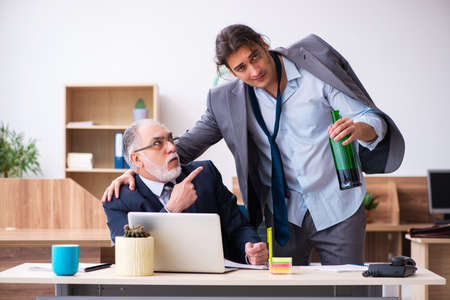 Old boss and male alcoholic employee in the office