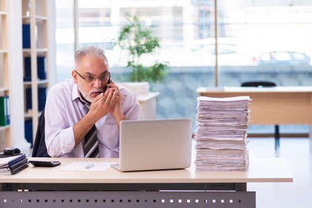 Aged businessman employee unhappy with excessive work