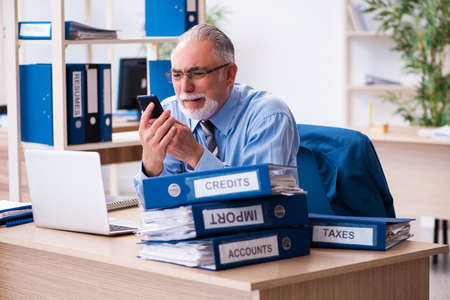 Old male bookkeeper unhappy with excessive work at workplace